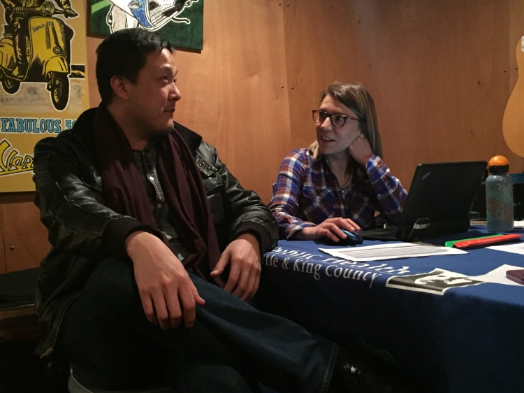 Enrollment assistance for Paul Shin, provided by Jen Covert of PHSKC, at Café Racer in Seattle